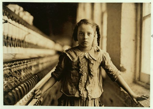 """One of the spinners in Whitnel Cotton Mfg. Co. N.C. She was 51 inches high. Had been in mill 1 year. Some at night. Runs 4 sides, 48 cents a day. When asked how old, she hesitated, then said """"I don't remember."""" Then confidentially, """"I'm not old enough to work, but I do just the same."""" Out of 50 employees, ten children about her size. Lewis Hine (1908). Courtesy the Library of Congress, D.C. Washington."""