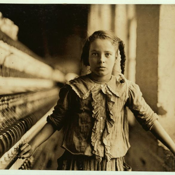 "One of the spinners in Whitnel Cotton Mfg. Co. N.C. She was 51 inches high. Had been in mill 1 year. Some at night. Runs 4 sides, 48 cents a day. When asked how old, she hesitated, then said ""I don't remember."" Then confidentially, ""I'm not old enough to work, but I do just the same."" Out of 50 employees, ten children about her size. Lewis Hine (1908). Courtesy the Library of Congress, D.C. Washington."